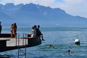 People enjoying the warm sunshine and refreshing water of Lake Geneva.